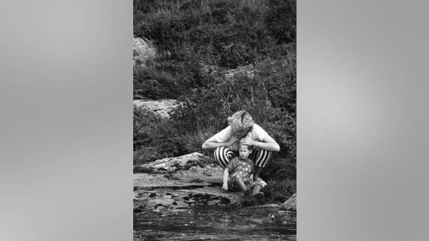 Princess Diana plays with Prince Harry by a stream.