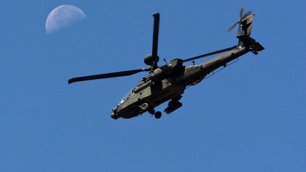 File photo - A U.S. Army Apache flies past the moon in the Zharay district of Kandahar province, southern Afghanistan June 11, 2012. (REUTERS/Shamil Zhumatov)