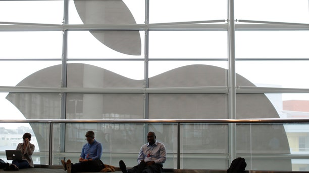 File photo - Attendees sit in front of an Apple logo at the Apple Worldwide Developers Conference (WWDC) 2013 in San Francisco, Calif. June 10, 2013. (REUTERS/Stephen Lam)