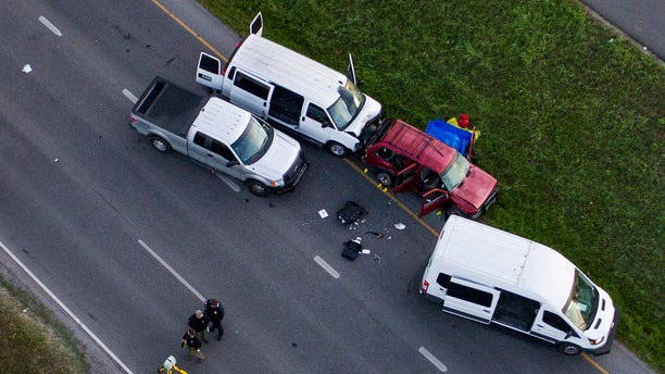 Officials investigate near a vehicle, center, where a suspect in the deadly bombings that terrorized Austin blew himself up as authorities closed in on him, in Round Rock, Texas, Wednesday, March 21, 2018.