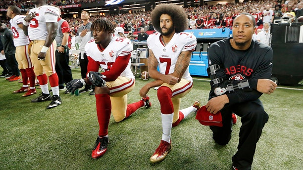 49ers quarterback Colin Kaepernick (center) takes a knee during an NFL game to protest police brutality.