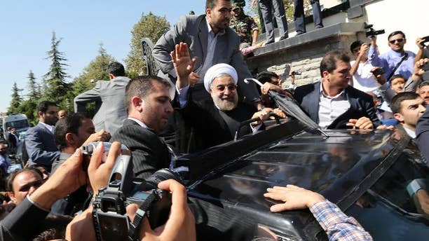 Iranian president Hassan Rouhani waves to supporters as his motorcade draws out of Tehran's Mehrabad Airport upon his arrival from New York, on September 28, 2013