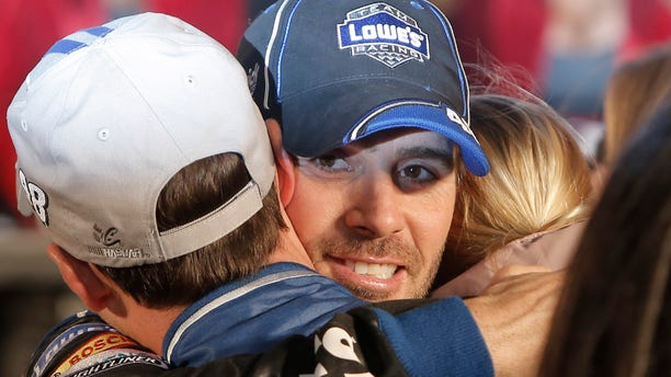Jimmie Johnson hugs his crew in victory lane after winning the NASCAR Sprint Cup series auto race at Texas Motor Speedway in Fort Worth, Texas, Sunday, Nov. 3, 2013. (AP Photo/Brandon Wade)