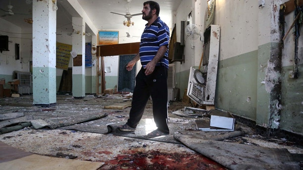 Aug. 25, 2014: A man walks past blood stains on the floor of the Imam Ali mosque after a suicide bomb attack in New Baghdad, Iraq.
