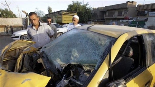 Friday: People inspect a damaged car at the scene of a bomb attack in Baghdad, Iraq. Two explosions on Thursday night in Sadr City neighborhood killed and wounded scores of people, police said.