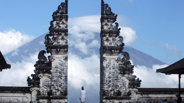 A Balinese man watches the Mount Agung volcano as he stands at a temple in Karangasem, Bali.