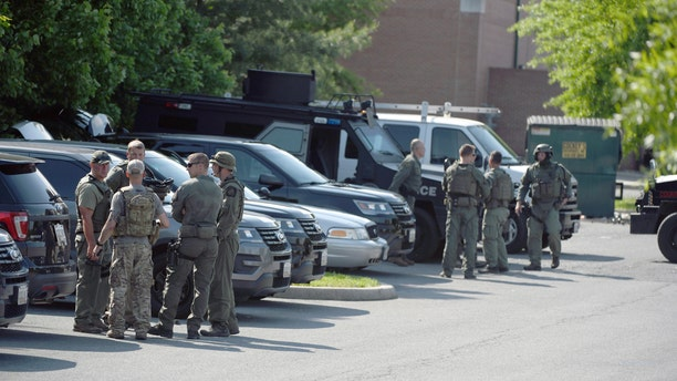 Tactical police stage in a Safeway parking lot on Belair Road near Chapel Road in response to the death of a Baltimore County police officer in Perry Hall, Md., May 21, 2018.