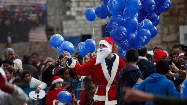 Dec. 24, 2014: A Palestinian dressed as Santa Claus holds balloons at Manger Square, outside the Church of the Nativity, traditionally believed by Christians to be the birthplace of Jesus Christ, in the West Bank city of Bethlehem on Christmas Eve.