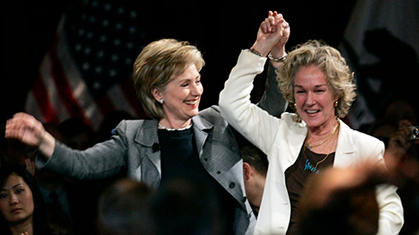 Image captured Hillary Clinton holdings hands with close friend and Esprit Clothing founder Susie Tompkins Buell.