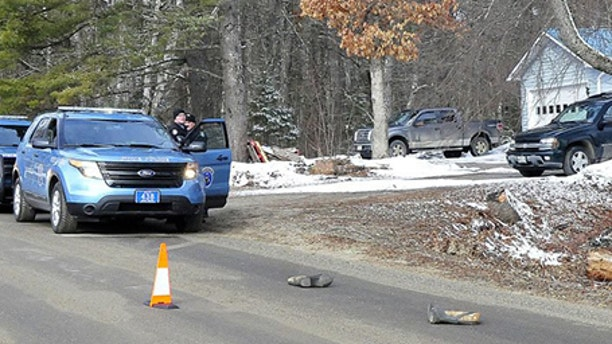 Two Maine State Police troopers consult with each other outside a residence Sunday on Winnecook Road in Burnham while investigating the death of Joyce Wood. A pair of boots lie in the road in foreground.