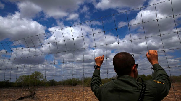 March 29, 2013: An immigration agent looks out at the desert near Falfurrias, Texas.
