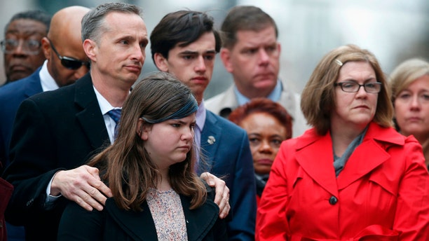 The family of Martin Richard, foreground from left, Bill, Jane, Henry and Denise, observe a moment of silence during a ceremony at the site where Martin Richard and Lingzi Lu were killed in the second explosion at the 2013 Boston Marathon, Sunday, April 15, 2018, in Boston.