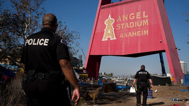 Officers are seen walking through the homeless camp outside Angel Stadium in late 2017, before the mass move-out.