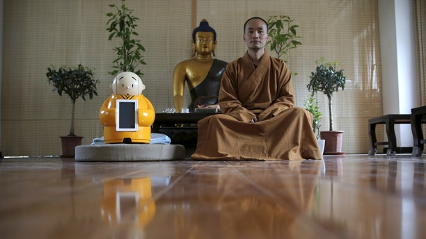 Master Xianfan sits next to robot Xian'er as he poses for photograph at Longquan Buddhist temple on the outskirts of Beijing, April 20, 2016. (REUTERS/Kim Kyung-Hoon)
