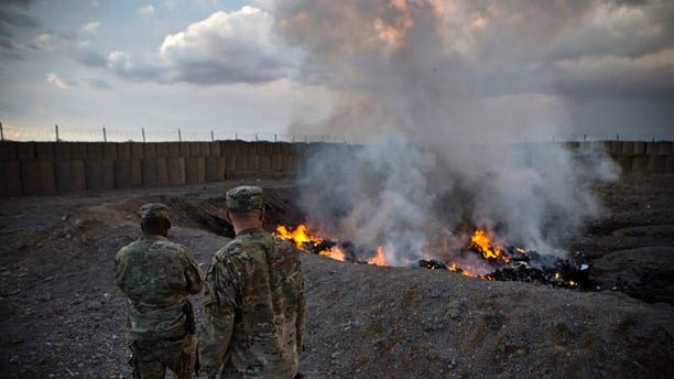 Feb. 4, 2013: U.S. Army soldiers watch garbage burn in a burn pit at Forward Operating Base Azzizulah in Maiwand District. Soldiers at FOB Sharana had to use a similar burn pit because incinerators were not completed.