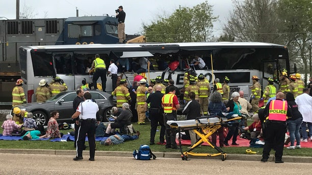 Biloxi, Miss., firefighters help passengers of a charter bus out of the damaged vehicle after the bus collided with a train Tuesday afternoon, March 7, 2017. (John Fitzhugh/The Sun Herald, via AP)
