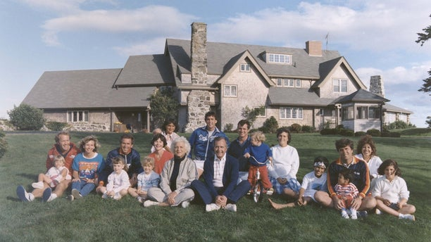 Portrait of the Bush family sitting in front of their home in Kennebunkport, Maine. BACK ROW: Maragret Bush (Marvin's wife), holding daughter Marshall, Marvin Bush, Bill LeBlond (Doro's Husband). FRONT ROW: Neil Bush holding son Pierce, Sharon (Neil's wife), George W. Bush holding daughter Barbara Bush, George Bush, Sam LeBlond (Doro's son), Doro Bush LeBlond, George P.