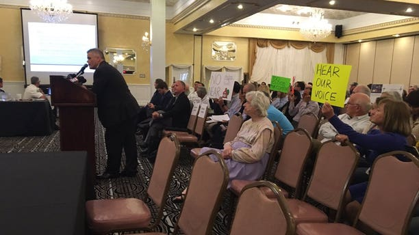 """Opponents of the """"guntry club"""" brought signs to the town hall meeting."""