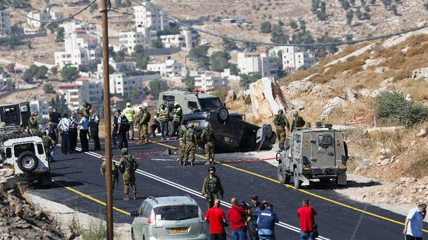 FILE - In this Friday, July 1, 2016, file photo, Israeli soldiers secure the scene of a car crash after a shooting attack near Hebron, West Bank, Friday, July 1, 2016. A few years ago, Islam al-Bayed spent seven months in an Israeli prison for allegedly throwing stones at Israeli troops. Now, the 26-year-old Palestinian man has become an unlikely symbol of coexistence after rescuing an Israeli family whose car crashed following a deadly roadside shooting by Palestinian militants in the West Bank. (AP Photo/Nasser Shiyoukhi)
