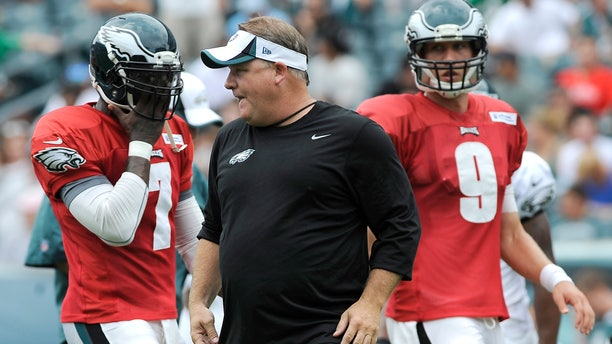 FILE - In this July 28, 2013, file photo, Philadelphia Eagles coach Chip Kelly, center, calls out a play as Michael Vick (7) and Nick Foles line up at NFL football training camp in Philadelphia. Despite Kelly's insistence that the Eagles run the same offense whether it's Vick or Foles under center, the two quarterbacks have obvious differences. (AP Photo/Michael Perez, File)
