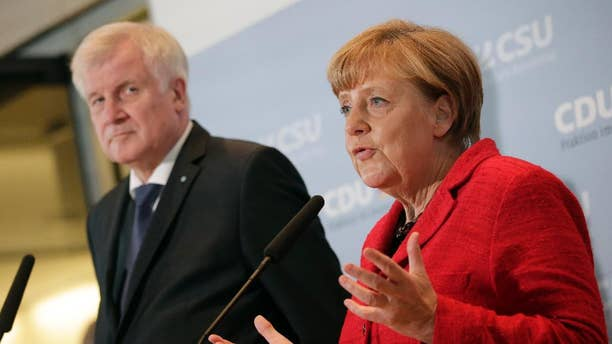 German Chancellor Angela Merkel, right, and the Governor of the German State of Bavaria, Horst Seehofer, left, address the media about the migrant influx.