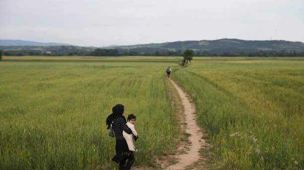 A woman walk with her baby on fields as a group of refugees and migrants leave the northern Greek border point of Idomeni, Greece, on Tuesday May 10, 2016. About 54,000 refugees and migrants are currently stranded in Greece as 10,000 are camped in Idomeni, after the European Union and Turkey reached a deal designed to stem the flow of refugees into Europe's prosperous heartland. (AP Photo/Petros Giannakouris)