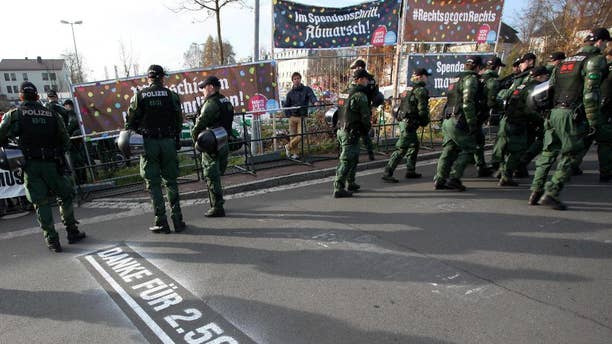 """In this picture taken Saturday, Nov. 15, 2014, police stand in front of banners reading """"Donate with every step, march"""", top left, and """"#right against right"""" top right, during a far-right march Wunsiedel, southern Germany. Letters on the ground say """"Thanks for euro 2,500!"""". After failing to prevent neo-Nazis from staging an annual pilgrimage to the birthplace of Adolf Hitler's deputy Rudolf Hess, the Bavarian town decided to change tack this year. Residents and businesses pledged to pay 10 euro (US dollar 12.50) for every meter the neo-Nazis walked, and motivational signs were erected along the route of Saturday's march. Inge Schuster, a spokeswoman for the town, said Tuesday that the stunt received """"a great response,"""" raising more than 10,000 euros for the group EXIT-Deutschland that helps people leave the neo-Nazi scene. (AP Photo/dpa, Fricke)"""