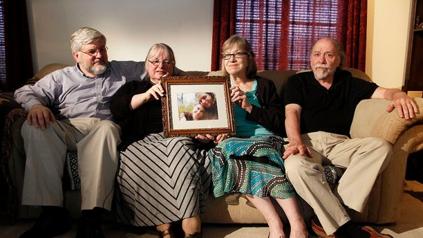 The Boyle and Cole family hold a picture of their kidnapped children.