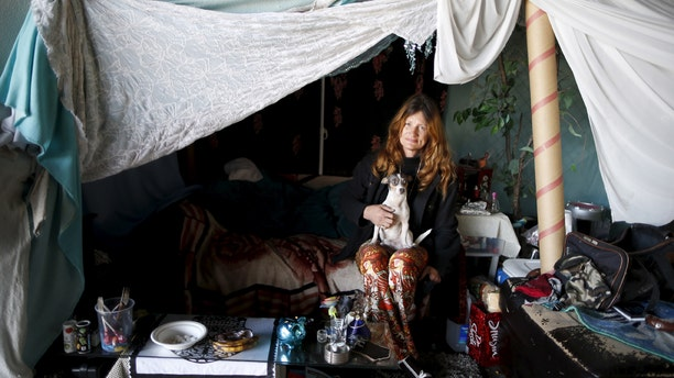 Karen Souza, 55, poses for a portrait with her dog Handsome by the tent in which she lives, under a freeway on a street in Los Angeles.