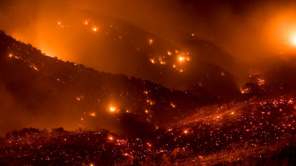 A hillside glows with embers as the Thomas fire burns through Los Padres National Forest near Ojai, Calif.