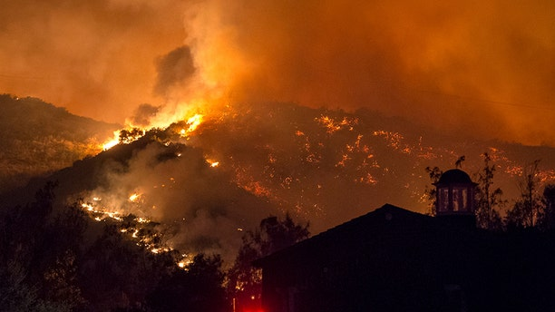 The fifth largest wildfire in California history expanded, ripping through dry brush atop a coastal ridge while crews struggled to keep flames from roaring down into neighborhoods amid fears of renewed winds.
