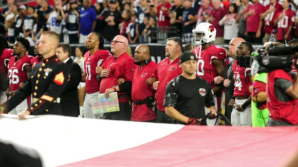 Arizona Cardinals standing in front of a giant flag during the national anthem.