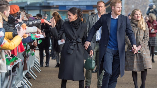 Meghan Markle and Prince Harry walk hand in hand as they greet fans outside of Cardiff Castle.