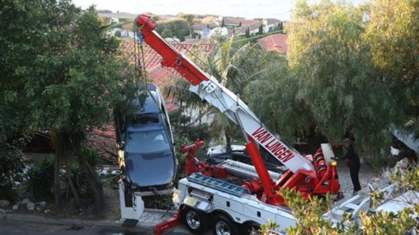 A crane removes a car that crashed off Palos Verdes Drive west and ended up on the roof of a home in Palos Verdes Estates, Calif. Wednesday, Feb. 3, 2016. Firefighters pulled the man from the damaged car and took him to a hospital, but he wasn't seriously hurt, and no one else was injured.  (Chuck Bennett/Daily Breeze via AP)