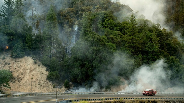 A fire truck passes a smoldering hillside as the Carr Fire burns along Highway 299 in unincorporated Shasta County, Calif.