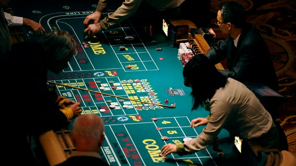 Sept. 18, 2013: In this photo, patrons play craps at a table at Mohegan Sun in Uncasville, Conn. As table games spread across the Northeast, resorts are using their own intelligence network more than ever to stay ahead of suspect players -- professional thieves as well as card counters -- who can easily hit multiple casinos in the span of a few days.