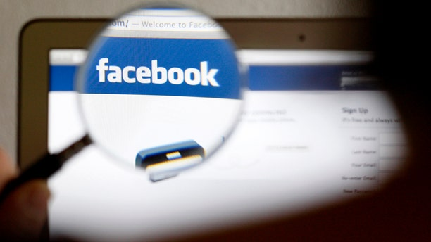 In this photo illustration, a Facebook logo on a computer screen is seen through a magnifying glass.