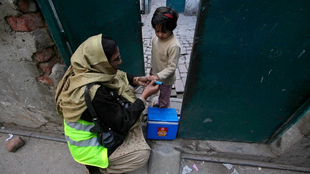 A female polio worker gives polio vaccine drops to a girl in Lahore December 20, 2012. (REUTERS/Mohsin Raza)