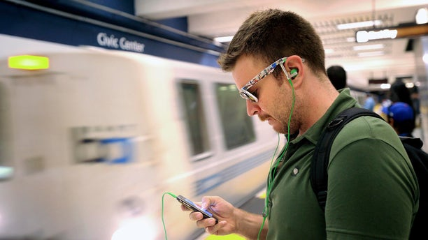 FILE: Aug. 13, 2011: A man checks his cell phone while waiting for a BART train at San Francisco's Civic Center station, in Calif.