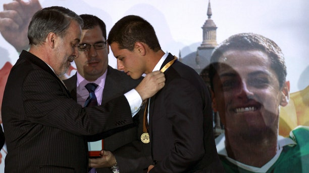 """Mexican soccer player Javier """"Chicharito"""" Hernandez, right, is awarded a medal from the governor of the state of Jalisco, Emilio Gonzalez Marquez,  during a ceremony in which Chicharito was named the 2011 Tourism Ambassador for the State of Jalisco, in Guadalajara, Mexico Thursday July 21, 2011. Chicharito  currently plays for the  English football club Manchester United. (AP Photo/Bruno Gonzalez)"""