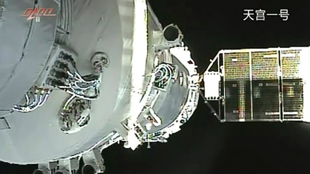 In this June 13, 2013, file image released by China's Xinhua News Agency, the Shenzhou-10 manned spacecraft is seen while conducting docking with the orbiting Tiangong-1 space module.