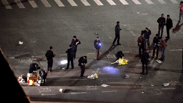 Mar 1. 2014: Police officers investigate the crime scene outside a railway station after an attack by knife wielding men leaving some 27 people dead in Kunming, in southwestern China's Yunnan province.