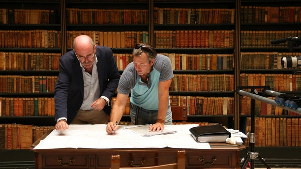 Darrell Miklos and Manuel Rodriguez go over ancient documents in a library in Jevez, Spain.