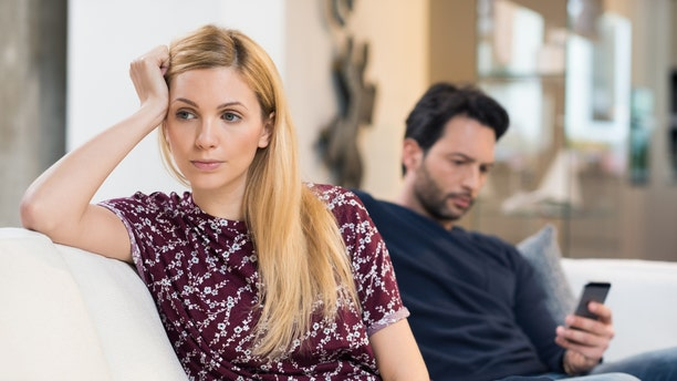 Young woman getting bored while man using phone in the background. Beautiful young woman feeling annoyed as man texting on phone. Young woman after an argument with her boyfriend in their living room.