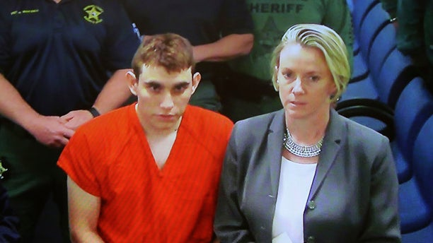 A video monitor shows school shooting suspect Nikolas Cruz, left, with his public defender Melisa McNeill making an appearance before Judge Kim Theresa Mollica in Broward County Court on Thursday in Fort Lauderdale, Fla.