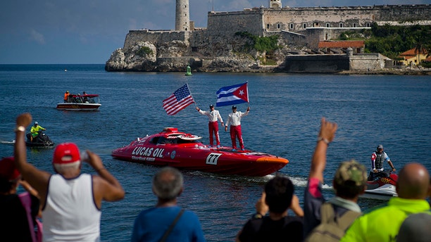 """Lucas Oil SilverHook powerboat drivers Nigel Hook, waving a Stars and Stripes, and James Johnson, waving a Cuban national flag, stand aboard their speedboat, backdropped by """"El Morro"""" castle, in Havana, Cuba, Thursday, Aug. 17, 2017. The team led by Hook, a California-based businessman, is claiming a record for a powerboat crossing from Florida to Cuba. The crew reports making it from Key West to Havana on Thursday in 1 hour and 18 minutes. (AP Photo/Ramon Espinosa)"""