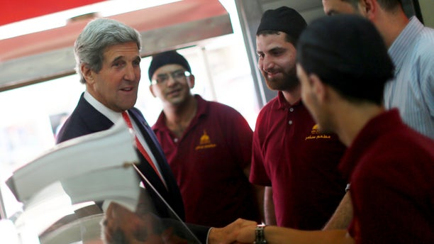 U.S. Secretary of State John Kerry shakea hands with Palestinian restaurant employees as he stops by for a snack after his meeting with Palestinian President Mahmoud Abbas in the West Bank city of Ramallah on Thursday, May 23, 2013. (AP Photo/Fadi Arouri, Pool)