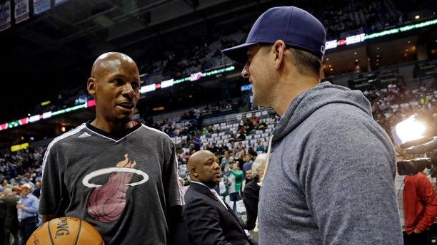 Miami Heat's Ray Allen, left, talks to Green Bay Packers quarterback Aaron Rodgers before the first half of Game 3 in their first-round NBA basketball playoff series against the Milwaukee Bucks, Thursday, April 25, 2013, in Milwaukee. (AP Photo/Morry Gash)