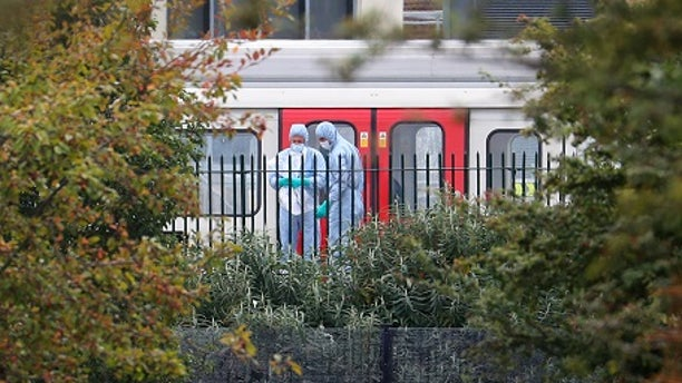 Investigators search next to a train at Parsons Green station in London.