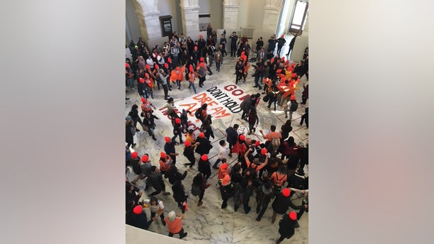 About 100 immigration protesters were seen gathering in the Russell Senate Office Building on Friday afternoon.